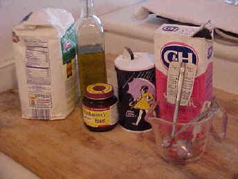 Ingredients for pizza: flour, olive oil, Fleischmann's yeast, salt, sugar, thermometer and cup.